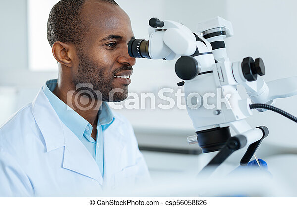 Charming dentist examining mouth cavity with microscope - csp56058826