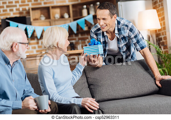 Charming Man Giving A Present To His Senior Mother