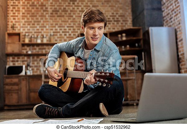 Charming man watching playing guitar tutorial. Improving skills ...