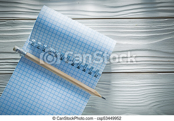 Checked spiral blank notepad pencil on white wooden board - csp53449952