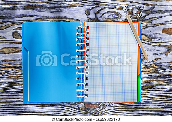 Checked spiral copybook pencil on wooden board - csp59622170