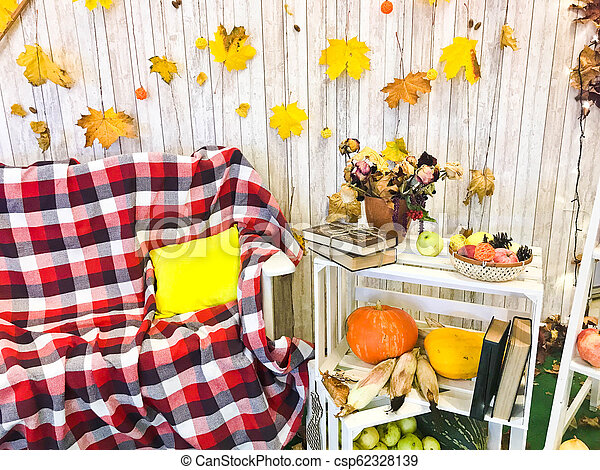 Checkered plaid on an armchair and a wooden table with vintage books tied with twine and a vase, herbarium, green apple on the background of wooden boards and yellow autumn leaves. - csp62328139