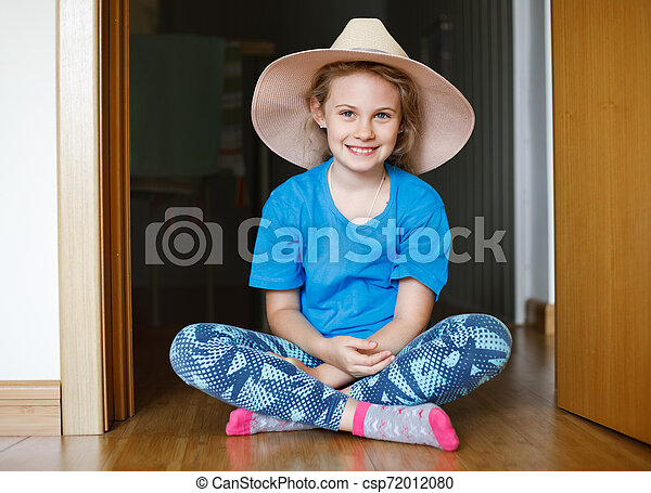 Cheerful 8 years old girl sitting on the floor in her room - csp72012080