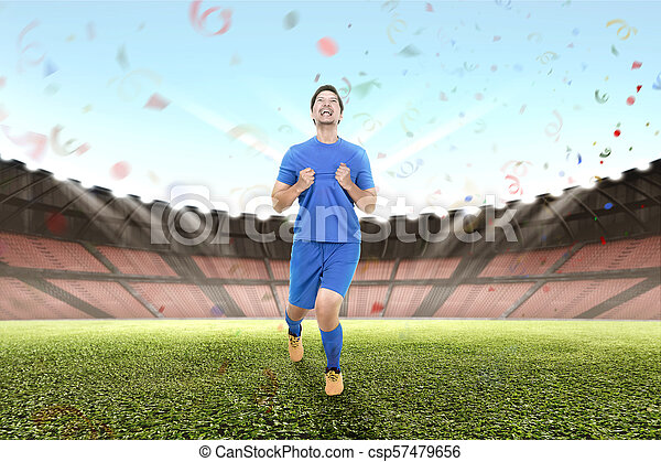 Cheerful asian male soccer player celebrate - csp57479656