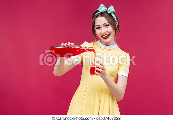 Cheerful attractive woman pouring juice from bottle into the glass - csp37487292