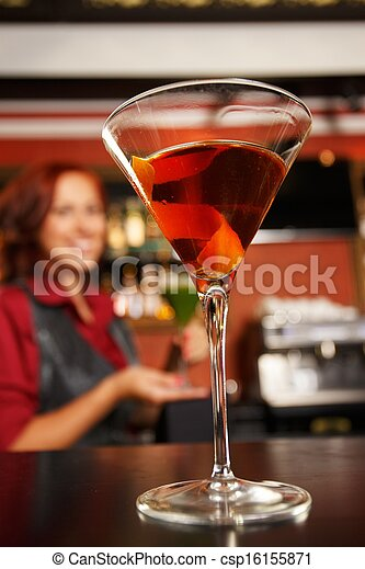 Cheerful barmaid with cocktail behind bar counter  - csp16155871
