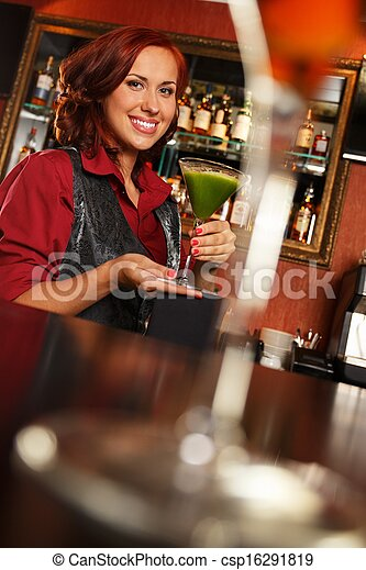 Cheerful barmaid with cocktail behind bar counter  - csp16291819