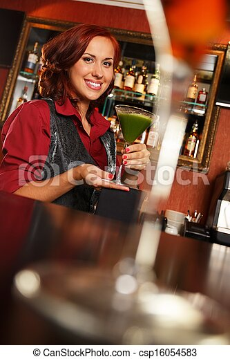 Cheerful barmaid with cocktail behind bar counter  - csp16054583