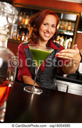 Cheerful barmaid with cocktail behind bar counter  - csp16054585