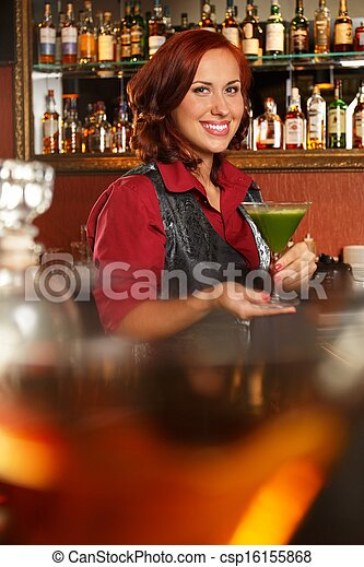 Cheerful barmaid with cocktail behind bar counter  - csp16155868