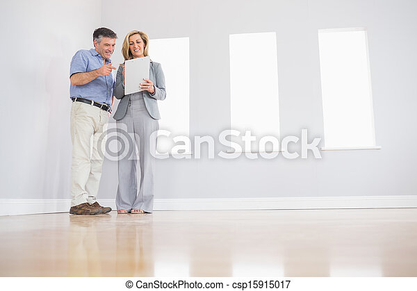 Cheerful blonde realtor showing an empty room and some documents to a potential attentive mature buyer - csp15915017
