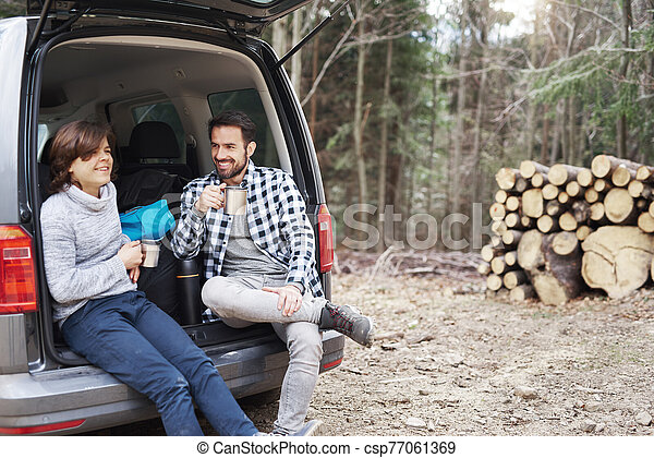 Cheerful boy and his dad drinking tea during spring hiking trip - csp77061369