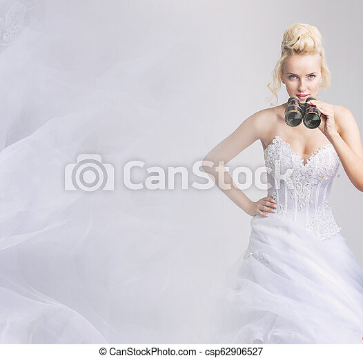 Cheerful bride looking through the binoculars - csp62906527