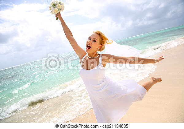Cheerful bride showing happiness at the beach - csp21134835