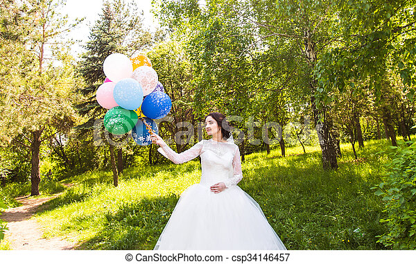 Cheerful bride with bunch of balloons - csp34146457