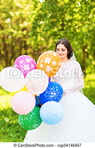 Cheerful bride with bunch of balloons - csp34146407