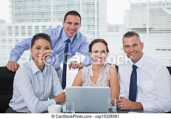 Cheerful colleagues around laptop posing - csp15338391