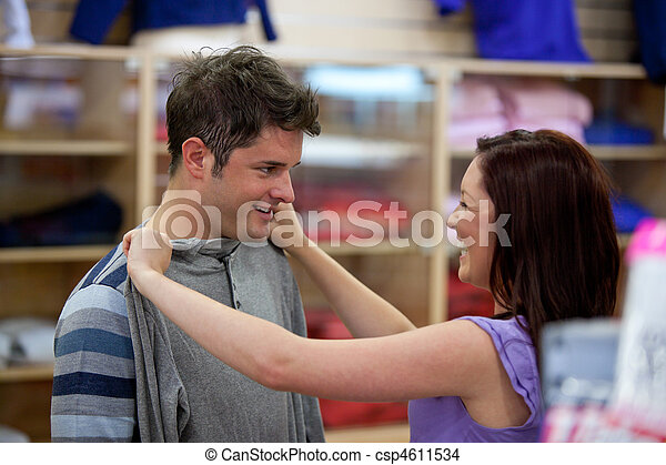 cheerful couple choosing clothes standing in the men department - csp4611534