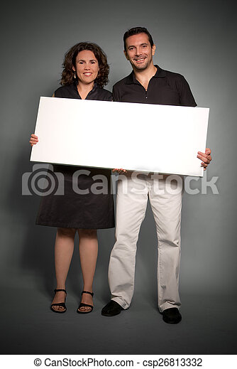 Cheerful couple holding a blank sign - csp26813332