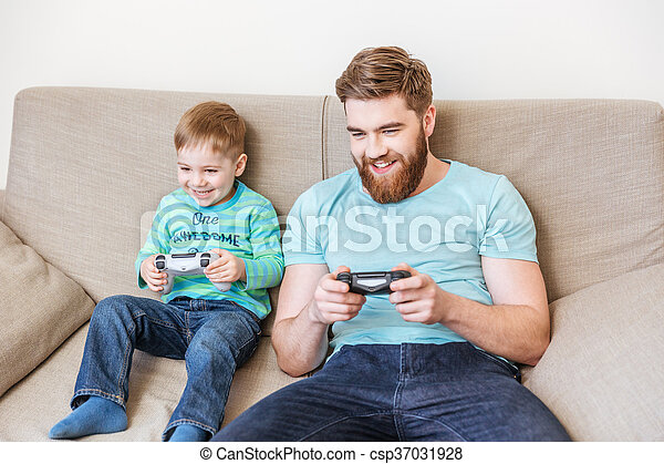 Cheerful dad and son playing computer games together - csp37031928