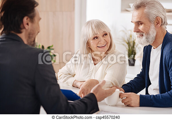 Cheerful elderly couple discussing contract at home - csp45570240