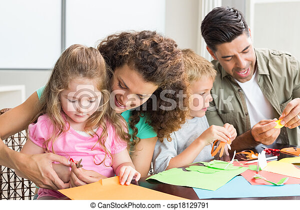 Cheerful family doing arts and crafts together at the table - csp18129791