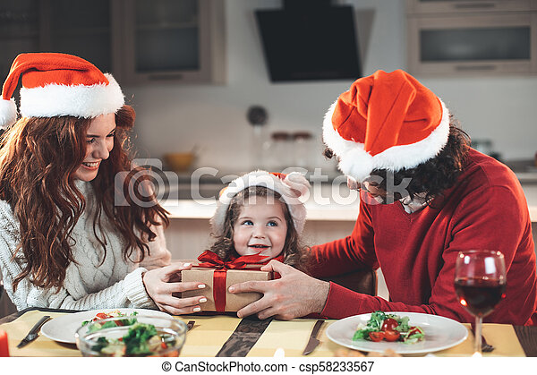 Cheerful father and mother giving present to their daughter - csp58233567