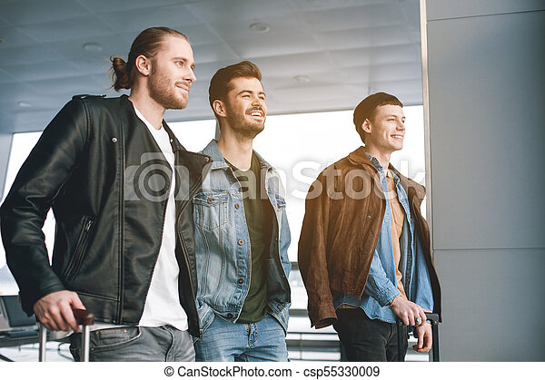 Cheerful friends speaking together in airport - csp55330009