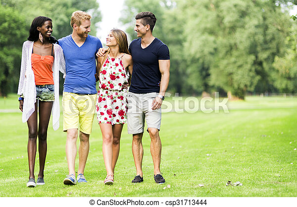 Cheerful friends walking in a park and having a good time - csp31713444