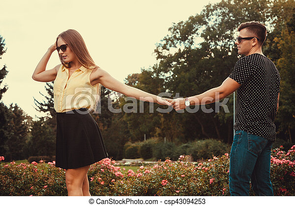 Cheerful girl holding hands in park. - csp43094253