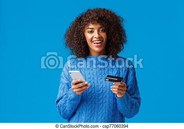 Cheerful good-looking smiling african-american woman buying online, shopping during discounts holiday season, smiling, holding smartphone and credit card, standing blue background - csp77060394