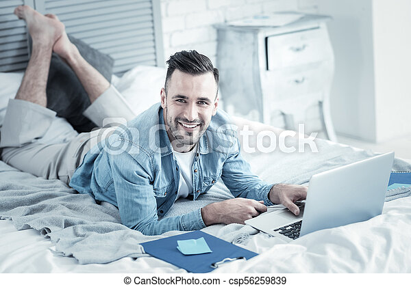 Cheerful handsome man doing an online course - csp56259839