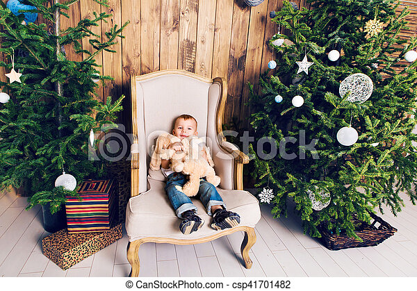Cheerful little boy playing with his toy by the Christmas tree - csp41701482