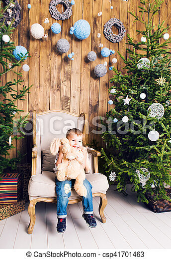 Cheerful little boy playing with his toy by the Christmas tree - csp41701463
