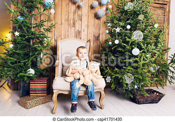 Cheerful little boy playing with his toy by the Christmas tree - csp41701430