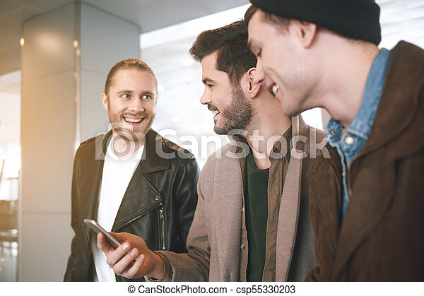 Cheerful male comrades speaking together - csp55330203