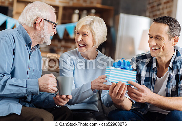 Cheerful Man Giving Present To His Elderly Mother