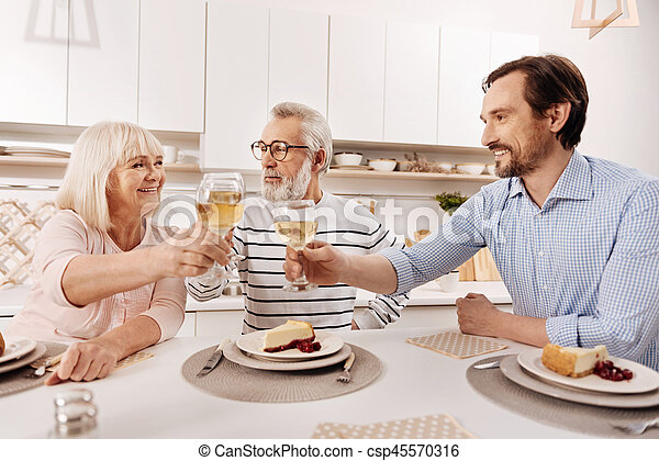 Cheerful man greeting his parents with holiday at home - csp45570316