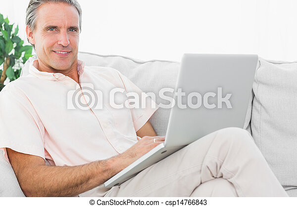 Cheerful man on his couch using laptop looking at camera - csp14766843