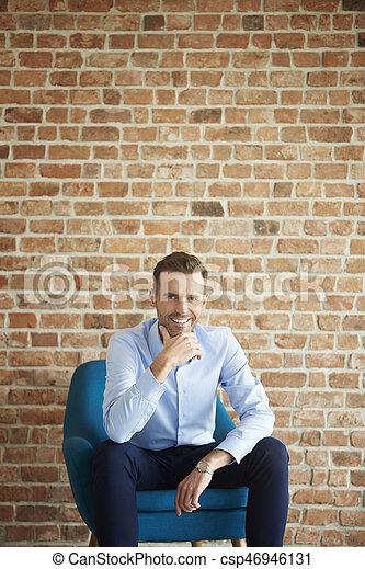 Cheerful man on the brick wall - csp46946131