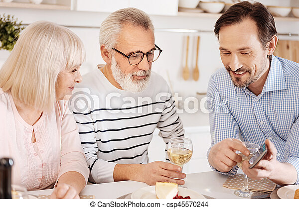 Cheerful mature son enjoying family dinner at home - csp45570244