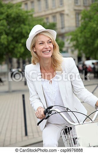Cheerful middle aged woman riding bike in town - csp9976888