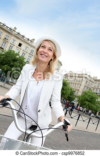 Cheerful middle aged woman riding bike in town - csp9976852