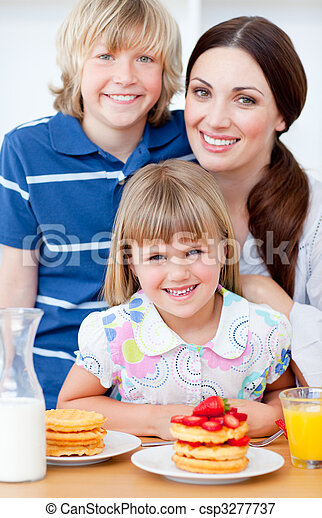 Cheerful mother and her children eating waffles with strawberries in the kitchen - csp3277737