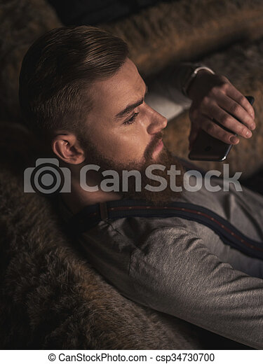 Cheerful old-fashioned guy is resting with telephone - csp34730700