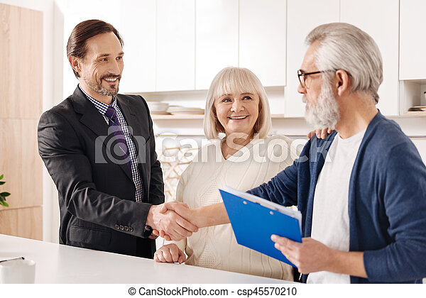 Cheerful real estate agent presenting contract to elderly couple - csp45570210
