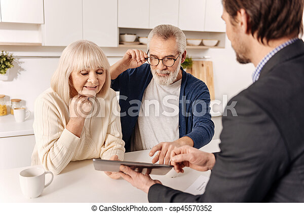 Cheerful retired couple using gadget with real estate agent - csp45570352