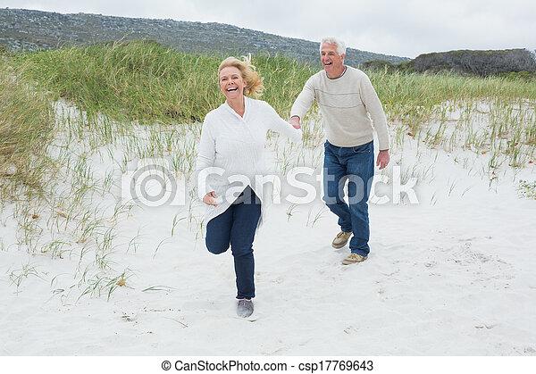 Cheerful senior couple running at beach - csp17769643