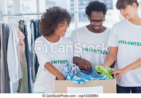 Cheerful volunteers taking out clothes from a donation box - csp14328884