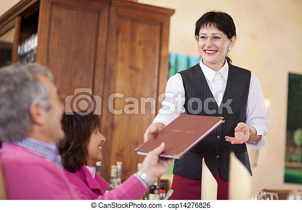 cheerful waitress passing the menu to guest - csp14276826